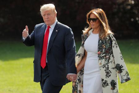 U.S. President Donald Trump gestures alongside First Lady Melania Trump before departing the White House