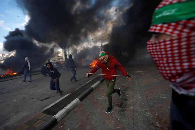 <p>Palestinian protesters run during clashes with Israeli troops at a protest against U.S. President Donald Trump's decision to recognize Jerusalem as the capital of Israel, near the Jewish settlement of Beit El, near the West Bank city of Ramallah, Dec. 7, 2017. (Photo: Mohamad Torokman/Reuters) </p>