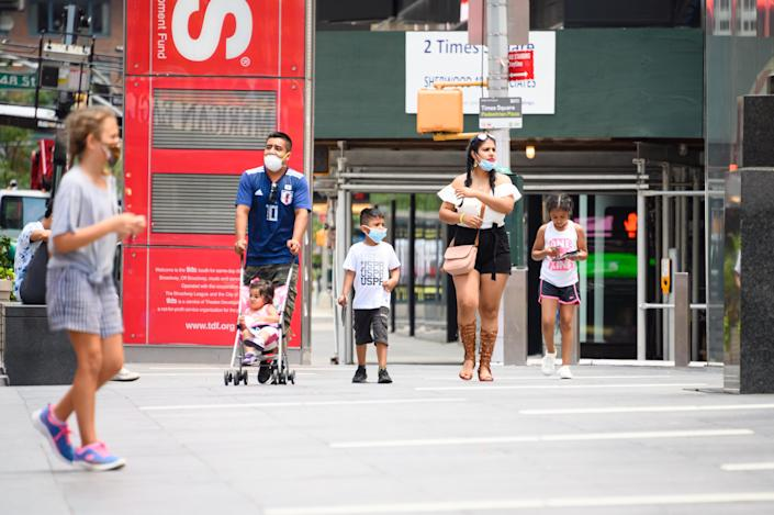 NEW YORK, NEW YORK - JULY 12: Family members wear face masks in Times Square as New York City moves into Phase 3 of re-opening following restrictions imposed to curb the coronavirus pandemic on July 12, 2020. Phase 3 permits the reopening of nail and tanning salons, tattoo parlors, spas and massages, dog runs and numerous other outdoor activities. Phase 3 is the third of four-phased stages designated by the state. (Photo by Noam Galai/Getty Images)