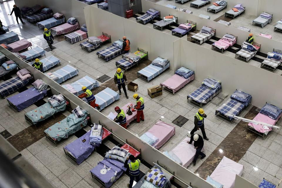 Workers preparing the Wuhan International Conference and Exhibition Centre. The space has been converted into temporary hospitals with a total of 1,000 beds. Source: Getty