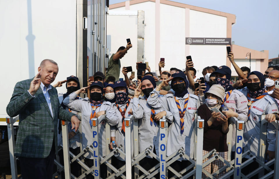 Turkey's President Recep Tayyip Erdogan salutes with scouts as he arrived to visit wildfires-affected forests in Marmaris, Mugla, Turkey, Saturday, July 31, 2021. Panicked tourists in Turkey hurried to the seashore to wait for rescue boats Saturday after being told to evacuate some hotels in the Aegean resort of Bodrum due to the dangers posed by nearby wildfires, Turkish media reported. The death toll from wildfires raging in Turkey's Mediterranean towns rose to six Saturday after two forest workers were killed, the country's health minister said.(Turkish Presidency via AP, Pool)