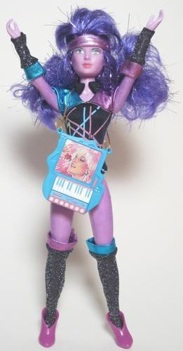 """<div class=""""caption-credit"""">Photo by: Hasbro</div><b>Original Synergy</b> <br> As the brains behind Jem and the Holograms, Synergy was the secret technology that helped Jerrica become Jem. The original toy was very aerobics-inspired, with a printed leotard, arm bands, socks, headband, and computer/keyboard. Her skin was a pinkish purple and there were metallic fibers in her purple hair."""