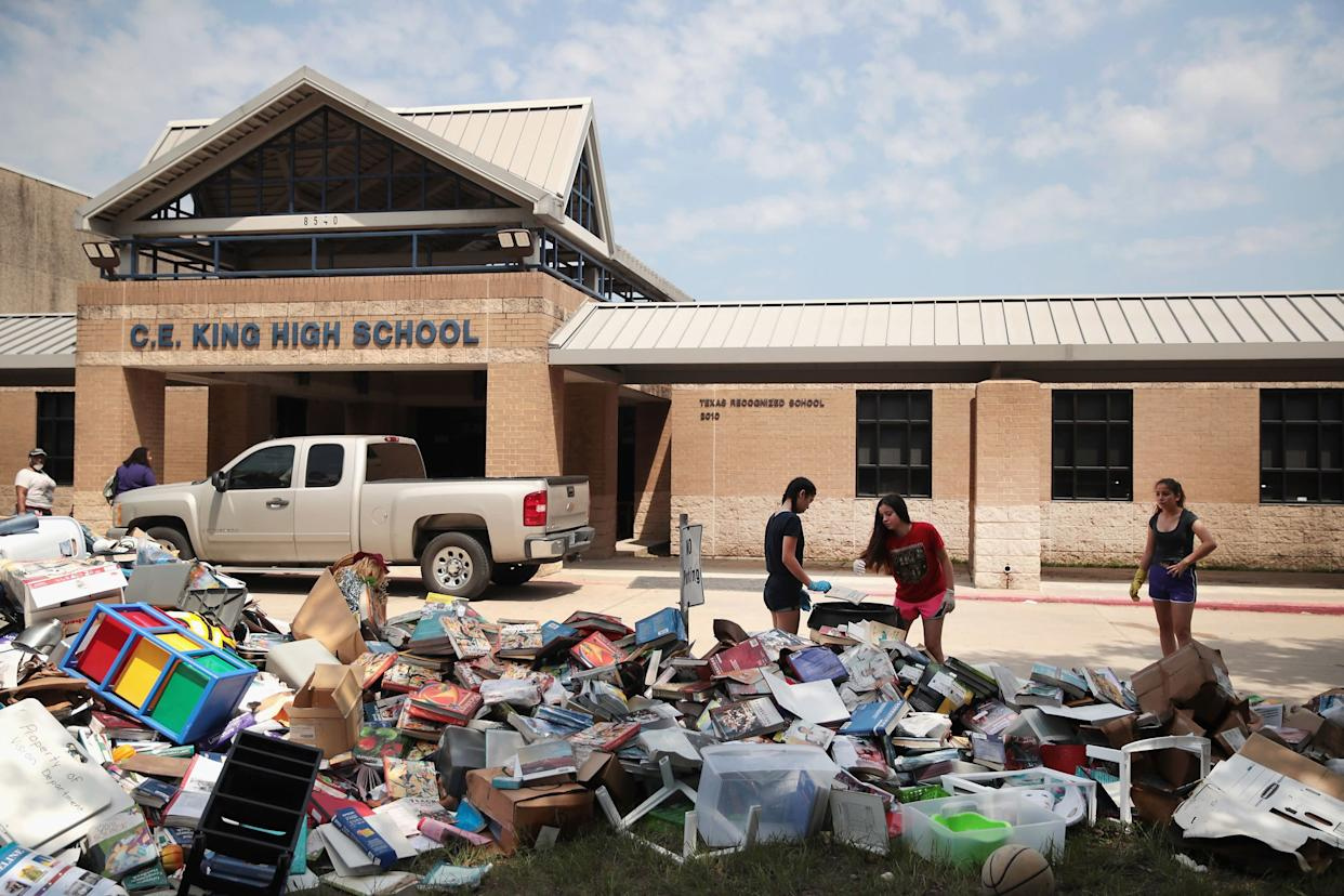 Volunteers place water damaged school furniture and text books on the front lawn of C.E. King High School.
