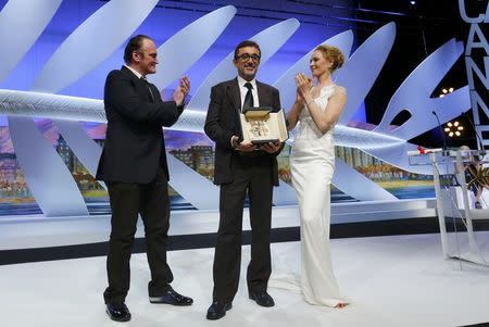 """Director Nuri Bilge Ceylan, Palme d'Or award winner for his film """"Winter Sleep"""", poses on stage surrounded by director Quentin Tarantino and actress Uma Thurman during the closing ceremony of the 67th Cannes Film Festival in Cannes"""