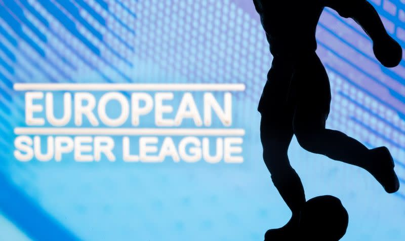 """A metal figure of a football player with a ball is seen in front of the words """"European Super League"""" in this illustration"""
