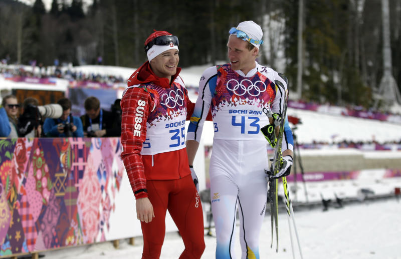 Gold medalist Switzerland's Dario Cologna, left, and silver medalist Sweden's Johan Olsson walk in the finish area after completing the men's 15K classical-style cross-country race at the 2014 Winter Olympics, Friday, Feb. 14, 2014, in Krasnaya Polyana, Russia. (AP Photo/Gregorio Borgia)
