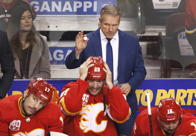 Calgary Flames interim coach Geoff Ward, center, acknowledges a referee during the first period of the team's NHL hockey game against the Ottawa Senators on Saturday, Nov, 30, 2019, in Calgary, Alberta. (Larry MacDougal/The Canadian Press via AP)
