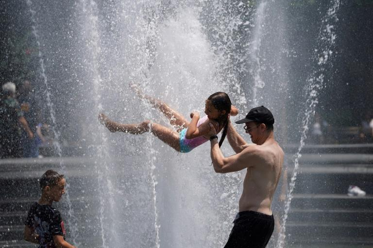 Americans like these cooling in a fountain in New York on July 19, 2019 have been urged to stay hydrated (AFP Photo/Timothy CLARY, TIMOTHY A. CLARY)