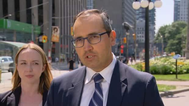 Lawyer Nader Hasan speaking with members of the media Friday afternoon. He's accompanied by lawyer Ryann Atkins. (CBC - image credit)
