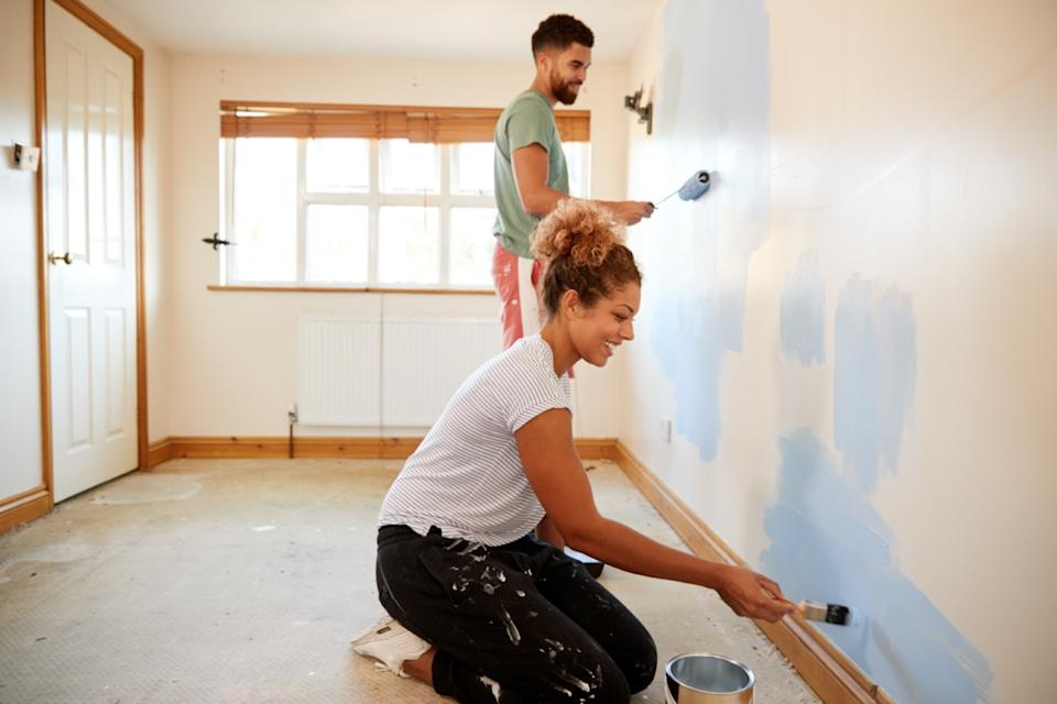 young couple painting wall with rollers