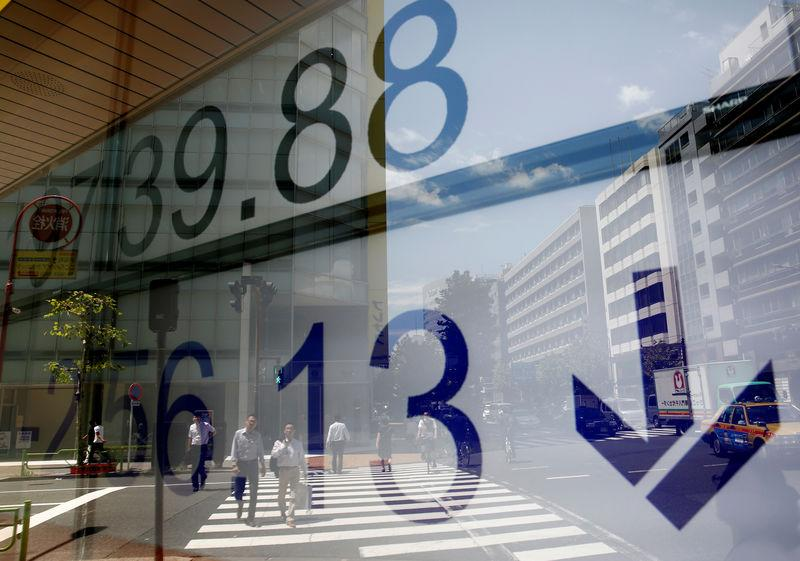 People are reflected on an electronic board showing Japan's Nikkei average outside a brokerage at a business district in Tokyo, Japan August 9, 2017. REUTERS/Kim Kyung-Hoon