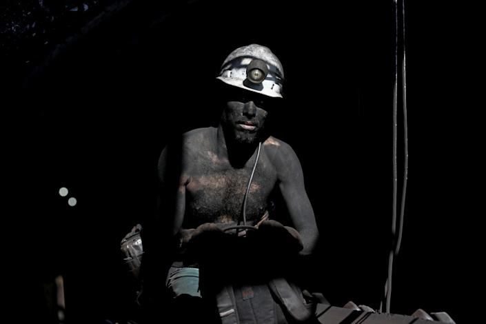 A man wears a mining helmet and is covered in soot.