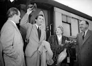 <p>The actor touches down in Paris by train in 1950. Here, he tips his hat to onlookers as he arrives at the railway station with his wife.</p>