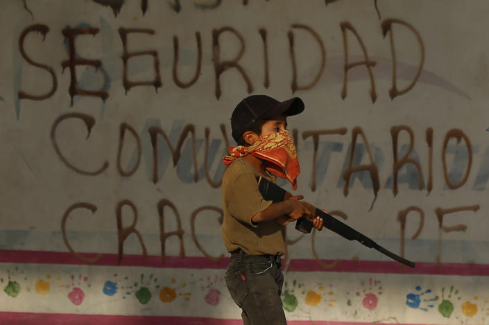 A child practices with a fake, wooden rifle during a display for the media in an attempt to attract the federal government's attention to the dangers his town faces from organized crime in Ayahualtempa, Guerrero state, Mexico, Wednesday, April 28, 2021. Residents are caught between two gangs: Los Ardillos and Los Rojos, as well as vigilante groups they distrust just as much. (AP Photo/Marco Ugarte)