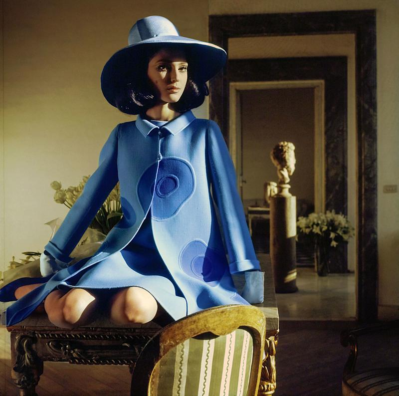 """Benedetta Barzini wears """"intarsia anemones from Mila Schön, big, stylized, set into a double-face wool coat of pale blue, the flowers deeper blue. The straw hat is by Mila Schön."""""""