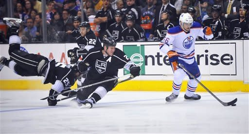 Edmonton Oilers center Teemu Hartikainen, right, controls the puck as Los Angeles Kings' Dustin Penner, left, Trevor Lewis (22) and Matt Greene defend during the first period of an NHL hockey game, Monday, April 2, 2012, in Los Angeles. (AP Photo/Richard Hartog)