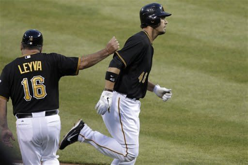 Pittsburgh Pirates' Garrett Jones (41) rounds third to greetings from coach Nick Leyva (16) after hitting a solo home run off Washington Nationals pitcher Edwin Jackson during the fourth inning of a baseball game in Pittsburgh on Tuesday, May 8, 2012. (AP Photo/Gene J. Puskar)