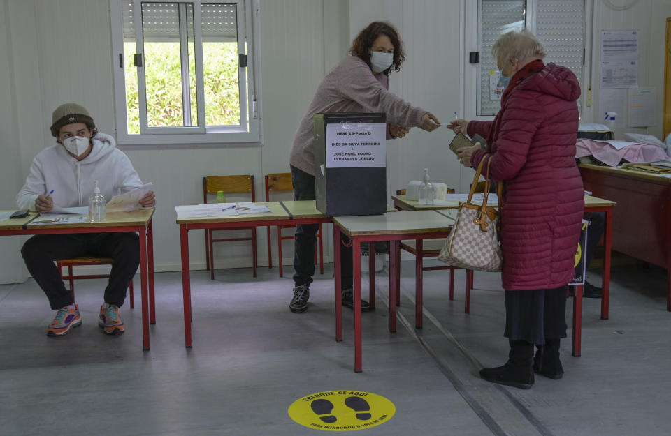 LISBON, PORTUGAL - JANUARY 24: A woman wearing a protective mask shows her ID at the polling station in the presidential election at Jorge Barradas School during the COVID-19 Coronavirus pandemic on January 24, 2021 in Lisbon, Portugal. The country's incumbent president, Marcelo Rebelo de Sousa, is running for a second term as head of state, a largely ceremonial role, albeit one with the power to dissolve parliament in the event of a political crisis. (Photo by Horacio Villalobos#Corbis/Getty Images)