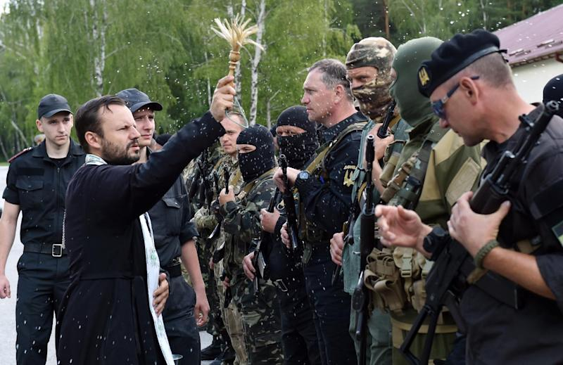 A priest blesses new volunteer recruits of the Ukrainian army 'Donbass' battalion during a military oath ceremony near the village of Novi Petrivtsi on June 23, 2014 (AFP Photo/Sergei Supinsky)