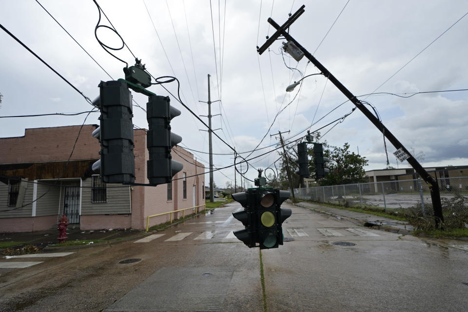 Traffic signals dangle close to the roadway from broken utility poles in Lake Charles, La., in the aftermath of Hurricane Laura, Sunday, Aug. 30, 2020. (AP Photo/Gerald Herbert)