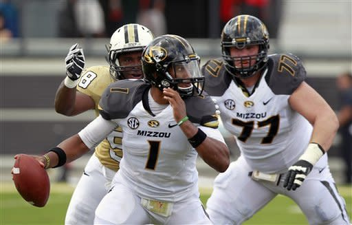 Missouri quarterback James Franklin (1) runs from the pocket away from Central Florida defensive lineman Troy Davis, left, as offensive linesman Evan Boehm (77) tries to block during the first half of an NCAA college football game, Saturday, Sept. 29, 2012, in Orlando, Fla. (AP Photo/John Raoux)