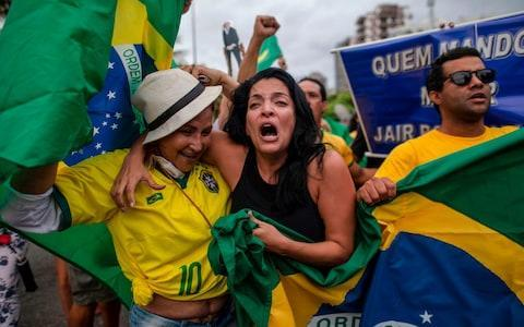 Supporters of Brazilian presidential candidate for the Social Liberal Party (PSL) Jair Bolsonaro cheer in front of the residential condominium where he lives, in Barra da Tijuca - Credit: AFP