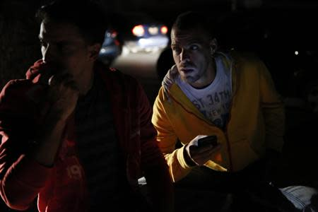 People wait on the street for the power to return after a blackout in Caracas December 2, 2013. REUTERS/Carlos Garcia Rawlins