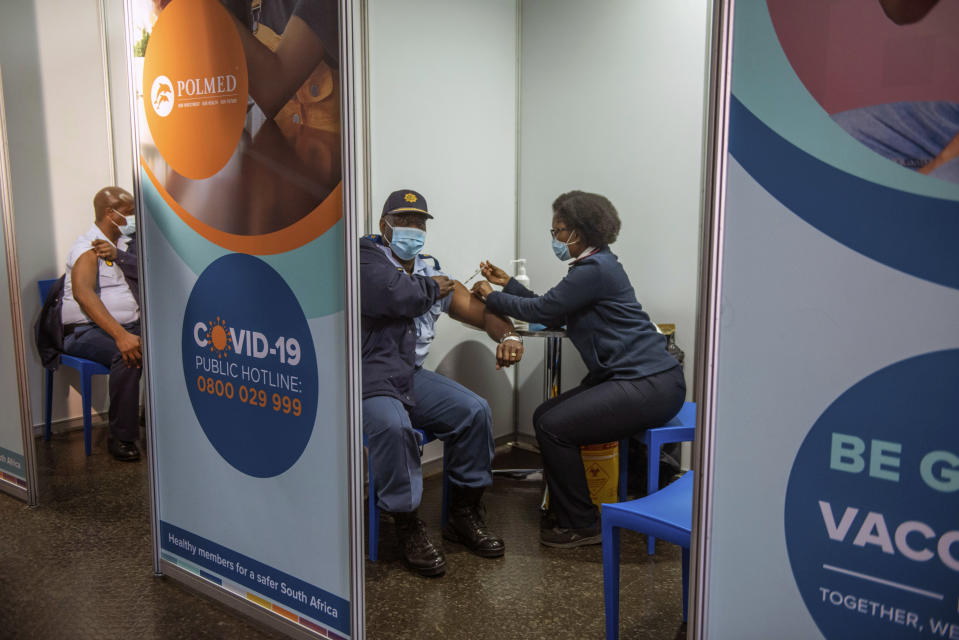 FILE - In this July 5 2021, file photo a policeman receives his Johnson & Johnson COVID-19 vaccine in Soweto, South Africa. New infections in South Africa rose to record levels in recent days, part of a rapid rise across the continent, and experts say the surge here has not yet peaked. South Africa reimposed several restrictions, and its vaccination drive is finding its feet after several stumbles. But even as the campaign gathers pace, experts say it's too late to reduce the deadly impact of the current spike. (AP Photo/Alet Pretorius/File)