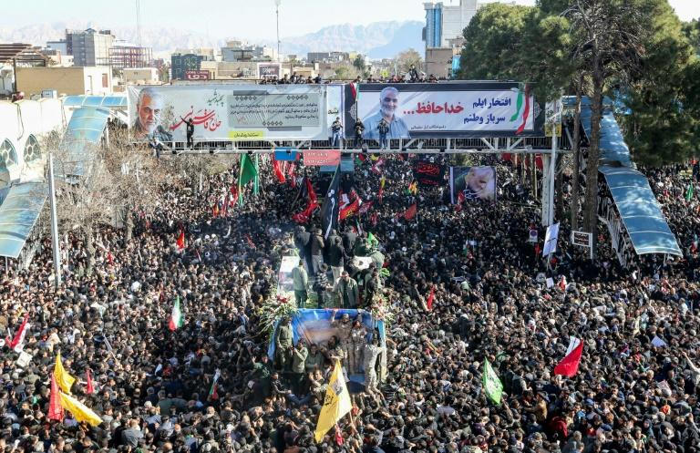 Iranian mourners gather around a vehicle carrying the coffin of slain top general Qasem Soleimani during the final stage of funeral processions, in his hometown Kerman (AFP Photo/ATTA KENARE)