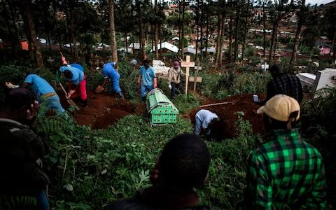 Family members react as they watch a victim of the Ebola virus being buried - Credit:  JOHN WESSELS/AFP
