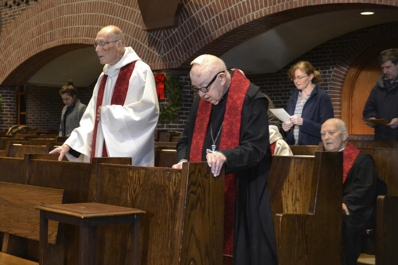 In this Dec. 26, 2019, photo, Benedictine monks of Saint Anselm Abbey celebrate mass in Manchester, New Hampshire. Monks at a Catholic college in New Hampshire have gone to court in a dispute with the school's board of trustees over an effort to limit their power. The two sides were in Hillsborough Superior Court on Monday, Jan. 6, 2020, over the lawsuit filed against the Saint Anselm College board last year. The unusual clash was set in motion when the board moved to take away the monks' ability to amend the school's bylaws. (AP Photo/Michael Casey).