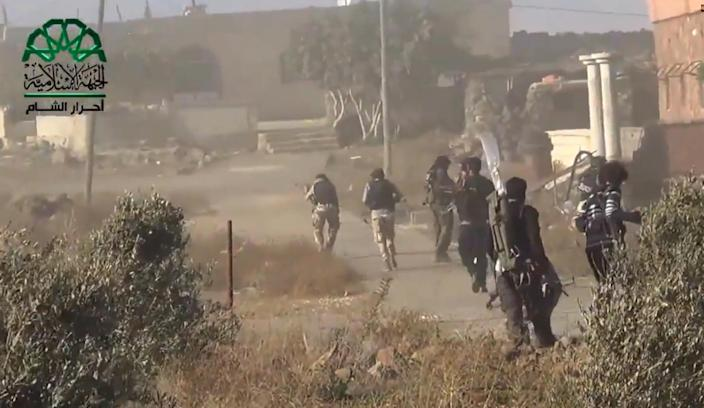 An image grab taken from a video released by Ahrar al-Sham and uploaded to YouTube on September 12, 2014 allegedly shows opposition fighters advancing as they capture a Syrian government forces position in the village of Khan Arnabeh (AFP Photo/)