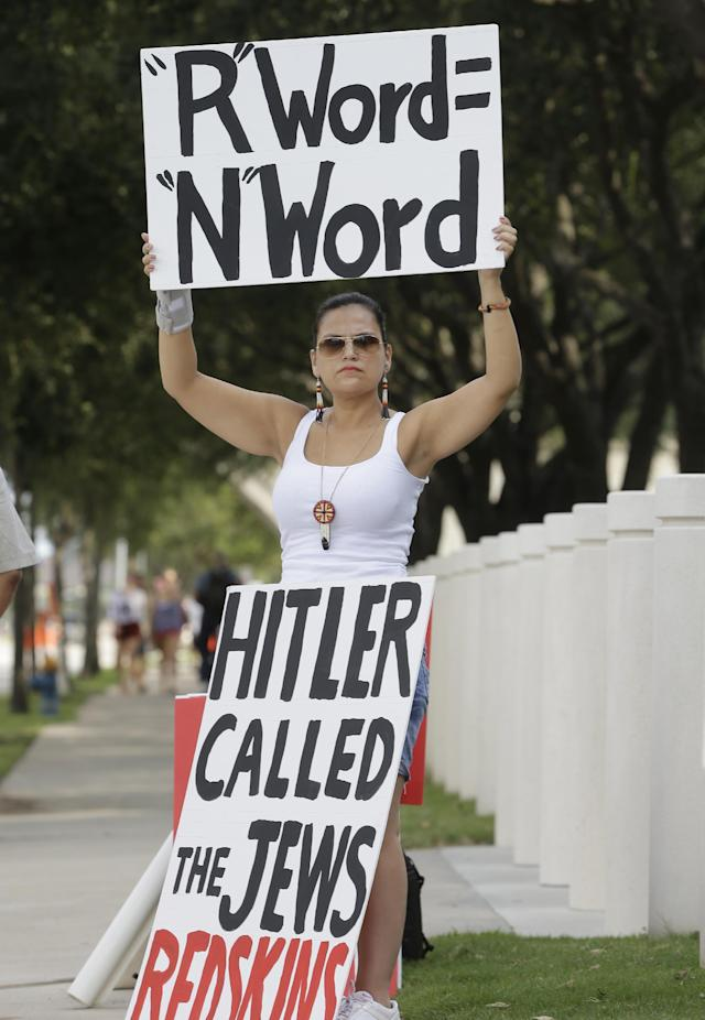 A woman protests against the Washington Redskins mascot name outside NRG Stadium before an NFL football game between the Washington Redskins and Houston Texans, Sunday, Sept. 7, 2014, in Houston. (AP Photo/Patric Schneider)