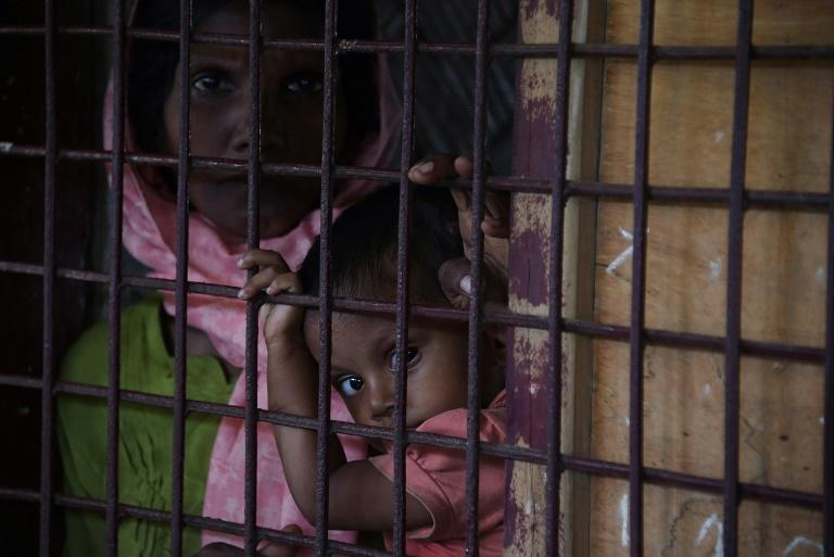 A Rohingya Muslim refugee and child look on as they sit in a school housing new refugees from Myanmar in Kutupalong refugee camp in the Bangaldeshi district of Ukhia on September 23, 2017