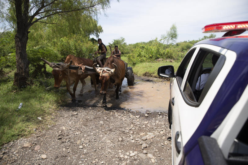 Men driving an ox cart pass agents from the new border patrol, near La Paz River on the border with Guatemala, in La Hachadura, El Salvador, Thursday, Sept. 12, 2019. The deployment of a new border patrol is part of an agreement between the Salvadoran government and acting U.S. Homeland Security Secretary Kevin McAleenan to slow the flow of migrants trying to reach the United States. (AP Photo/Moises Castillo)