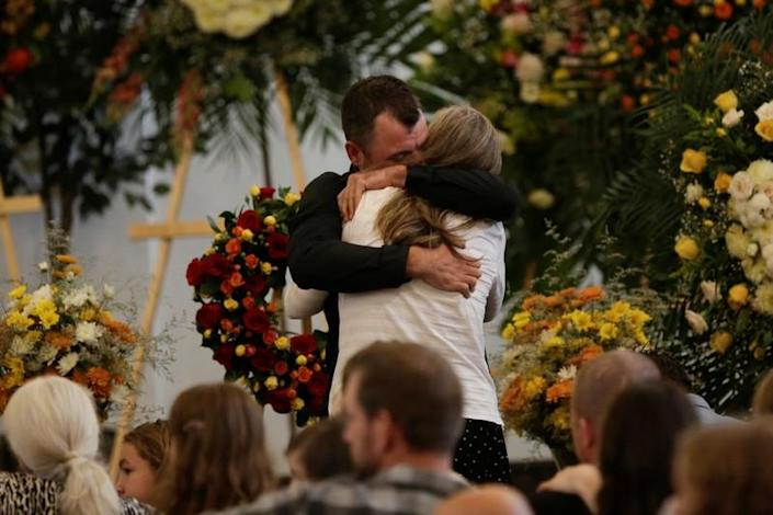 Tyler Johnson, husband of Christina Marie Langford Johnson, who was killed by unknown assailants, hugs a relative during her funeral service, before a burial at the cemetery in LeBaron, Chihuahua