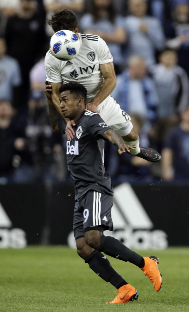 Sporting Kansas City midfielder Graham Zusi (8) heads the ball over Vancouver Whitecaps forward Anthony Blondell (9) during the first half of an MLS soccer match in Kansas City, Kan., Friday, April 20, 2018. (AP Photo/Orlin Wagner)