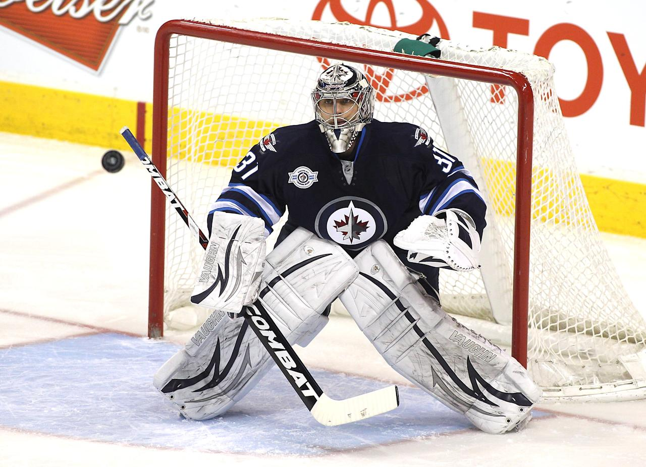 WINNIPEG, CANADA - MARCH 16: Ondrej Pavelec #31 of the Winnipeg Jets keeps his eye on the puck as it flies through the air during a game against the Washington Capitals in NHL action at the MTS Centre on March 16, 2012 in Winnipeg, Manitoba, Canada. (Photo by Marianne Helm/Getty Images)
