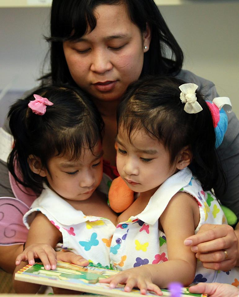 PALO ALTO, CA - OCTOBER 31:  Conjoined twins Angelica (R) and Angelina Sabuco (L) play a game with their mother Ginady (C) during a press conference at the Lucile Packard Children's Hospital at Stanford on October 31, 2011 in Palo Alto, California.  Two year-old conjoined twins Angelica and Angelina Subaco who are connected at the chest and abdomen are preparing for separation surgery by Dr. Gary Hartman. The surgery will last between 6 and 8 hours that is followed by three hours of reconstructive surgery for each girl. (Photo by Justin Sullivan/Getty Images)