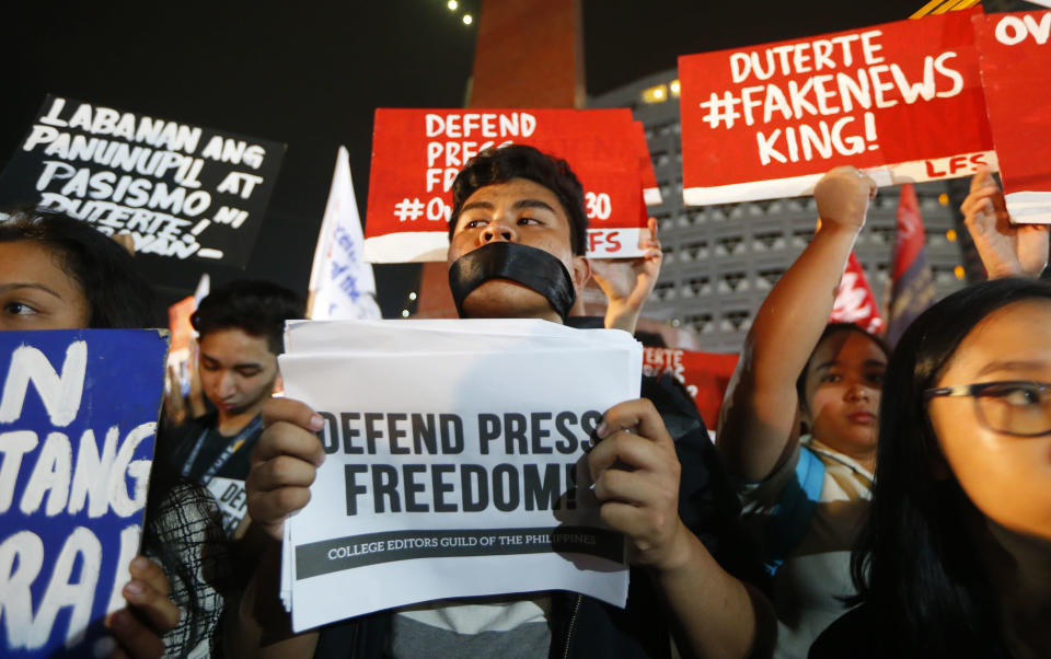FILE - In this Jan. 19, 2018, file photo, journalists and supporters display their messages during a protest against the recent Securities and Exchange Commission's revocation of the registration of Rappler, an online news outfit, northeast of Manila, Philippines. (AP Photo/Bullit Marquez, File)