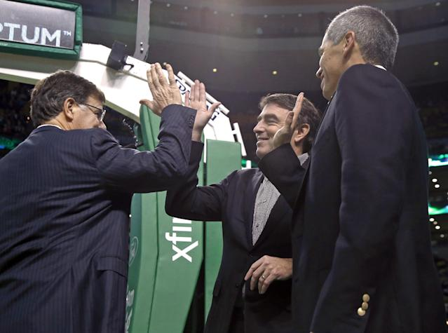 In this photo taken on Dec. 18, 2013, Boston Celtics managing partner Wyc Grousbeck, center, high-fives venture capitalist Bob Higgins, left, and team co-owner Mark Wan, right, during a break in the action at an NBA basketball game in Boston. Grousbeck and a group featuring a dozen of his co-owners in the NBA franchise have invested $21 million into Formula E, an all-electric auto racing series that has already attracted interest from environmental celebrities like Leonardo DiCaprio and Richard Branson. The circuit is scheduled to debut in Beijing in September and continue on the streets from Miami to Monaco in a 10-race, Formula One-style championship. (AP Photo/Elise Amendola)