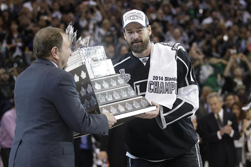 Los Angeles Kings right wing Justin Williams, right, is handed the Conn Smythe Trophy by NHL commissioner Gary Bettman, left, after the Kings beat the Rangers in Game 5 of the NHL Stanley Cup Final series Friday, June 13, 2014, in Los Angeles. (AP Photo/Jae C. Hong)
