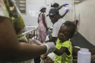 A child injured by the recent 7.2 magnitude earthquake is treated at the Immaculee Conception hospital in Les Cayes, Haiti, Thursday, Aug. 19, 2021. (AP Photo/Joseph Odelyn)