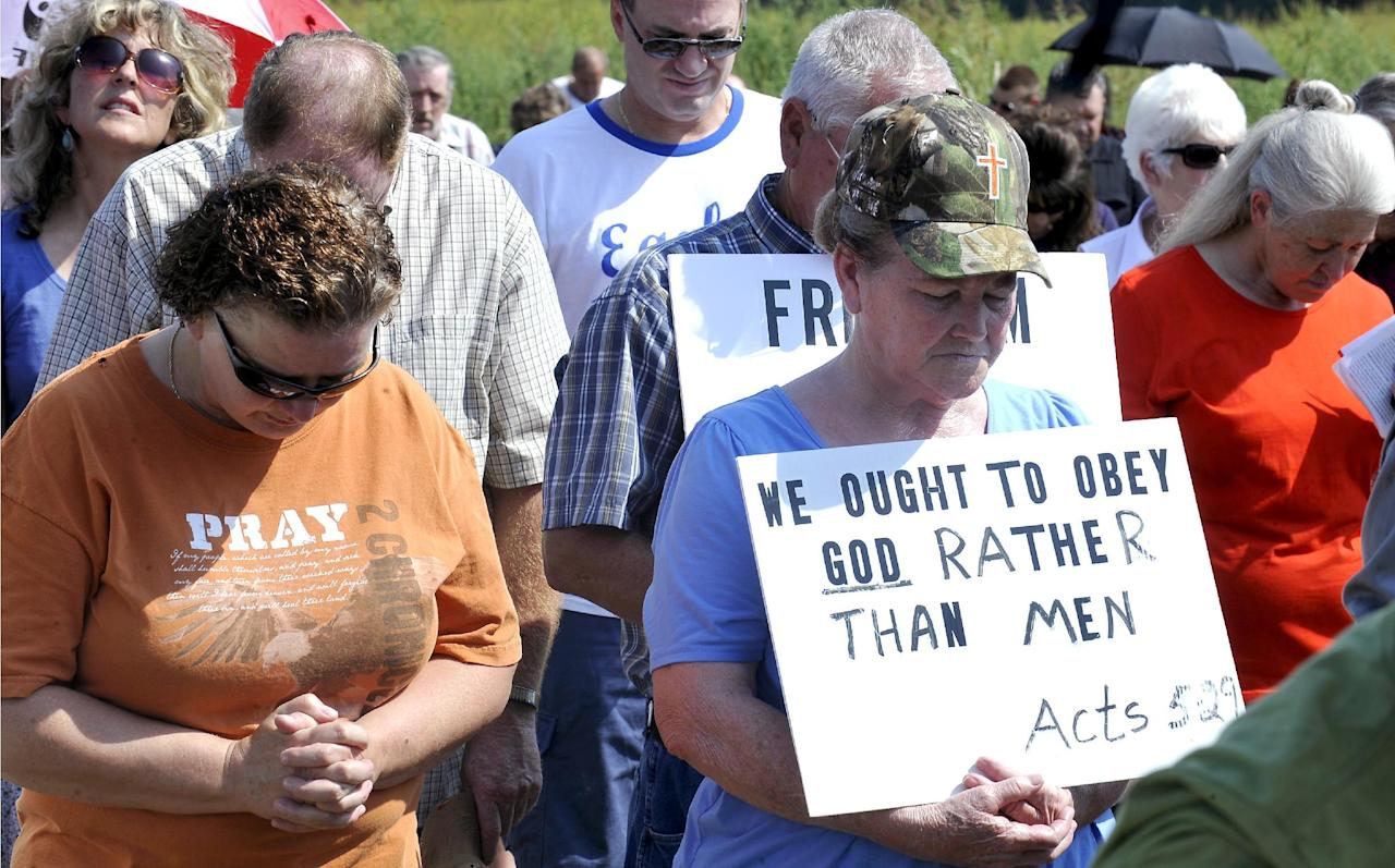 Supporters pray at the Carter County Detention Center for Rowan County clerk Kim Davis, who remains in jail for contempt of court in Grayson, Kentucky September 5, 2015. Around 200 supporters gathered outside a Kentucky jail on Saturday to support a county clerk held there for defying a federal judge's order to issue marriage licenses to same-sex couples. REUTERS/Chris Tilley