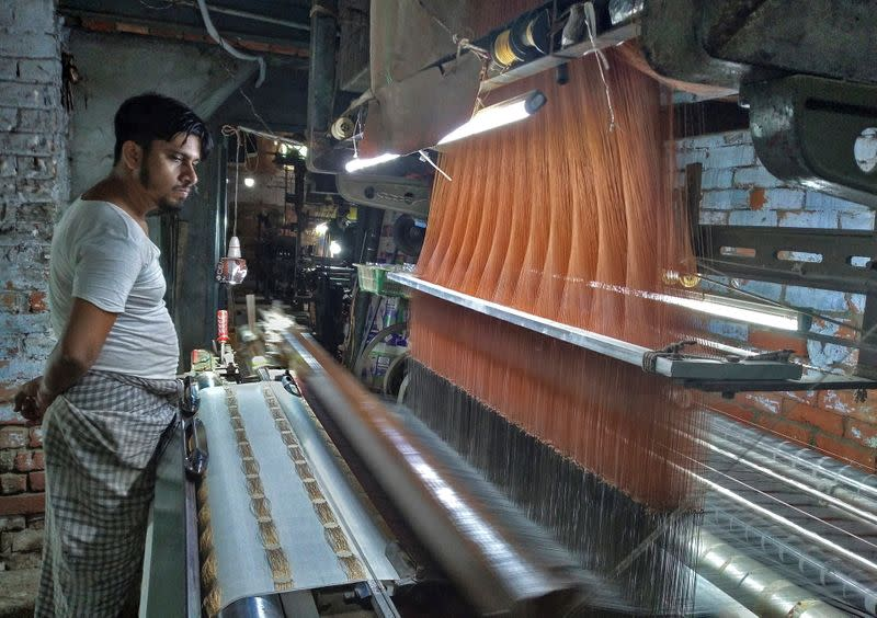 A weaver works on a power loom at factory in Varanasi