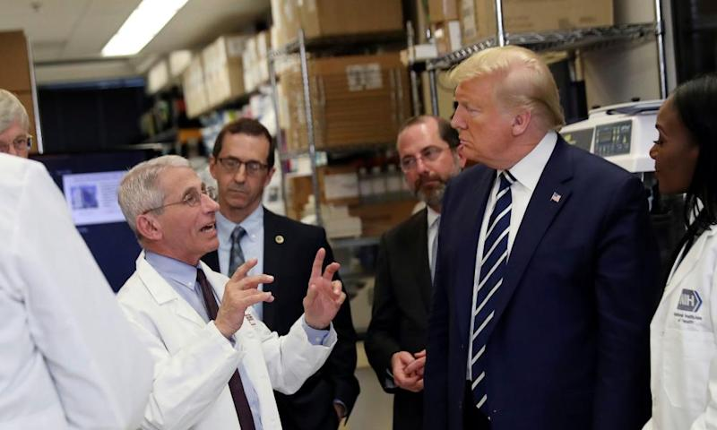 Dr Fauci speaks to US President Donald Trump during a tour of the National Institutes of Health.