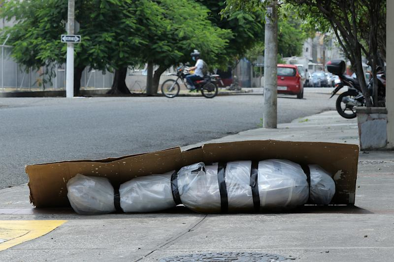 An abandoned corpse wrapped in plastic and covered with cardboard lies on the sidewalk in Guayaquil, Ecuador.. Source: Getty Images