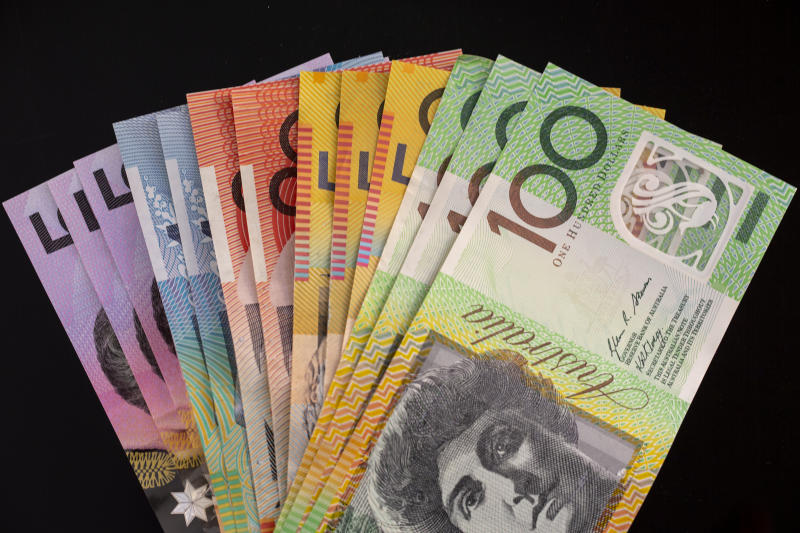 A variety of Australian money on a black background.