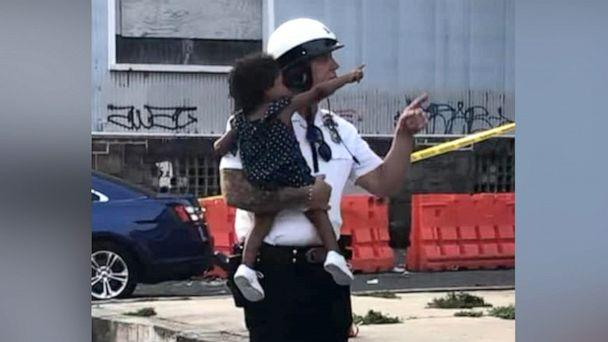 PHOTO: Sgt. Ed Pisarek, of The Philadelphia Highway Patrolm helping escort a baby from one of the daycare center during the shootout. (Philadelphia Fraternal Order of Police Lodge 5)