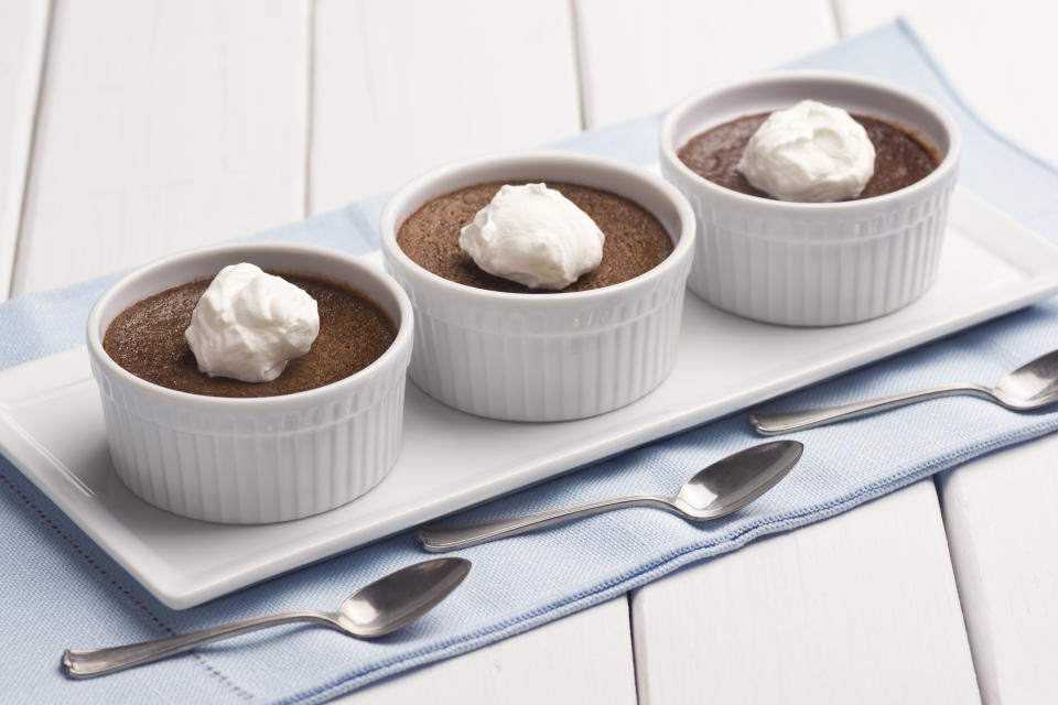 Three servings of the French dessert, chocolate pot de creme sit on a plate.